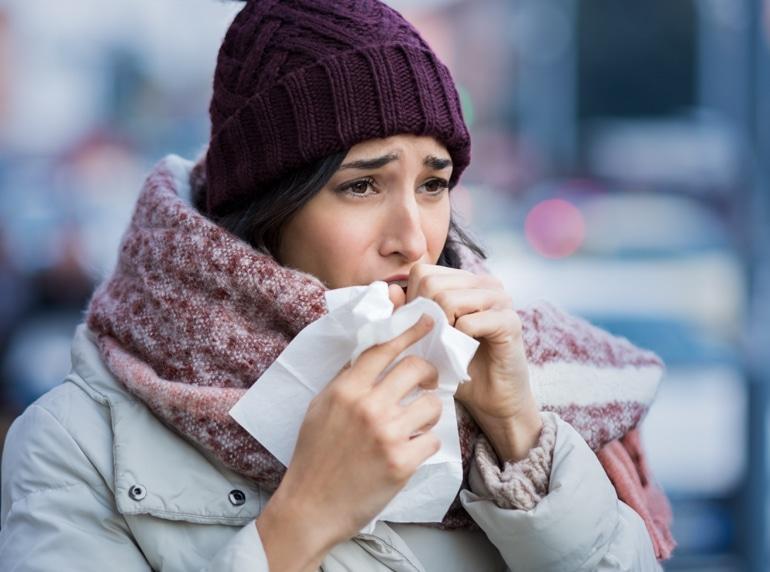 ახალგაზრდა ქალი ზამთეის ტანსაცმლით ახველებს